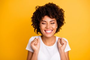 Close up photo of beautiful, happy woman on yellow vibrant background